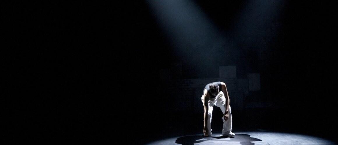 Danser in Spotlight op het podium. Witte broek, ontbloot bovenlichaam.